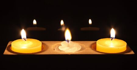 two yellow candles with a white flower in the centre Stock Photo