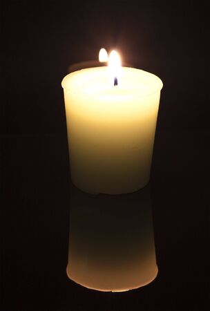 a white candle lit against a black background, with reflection