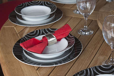 a red and black theme place setting on wooden table