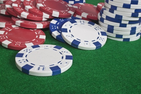some multi coloured poker chips scattered on a green beize Stock Photo - 8371586
