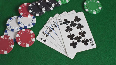 a royal flush of clubs with poker chips scattered
