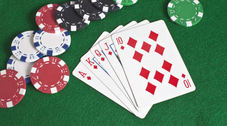 a royal flush of diamonds with poker chips scattered