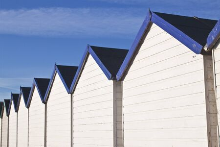 rows of wooden white and blue beach huts