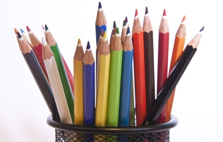 some multi coloured pencils standing in a wire pot
