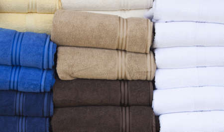 some towels stacked up in various colours photo