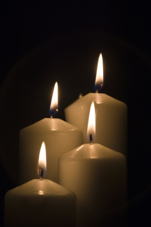 some white candles lit, against black background Stock Photo