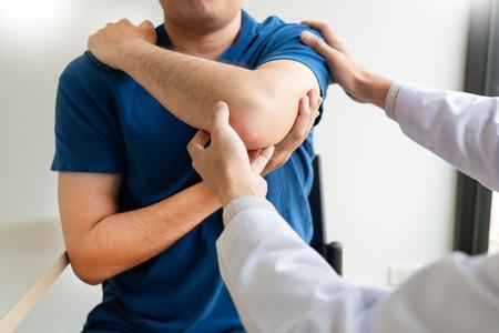 Physiotherapeuten-Arbeitskonzept, Arzt und Patient leiden oder Chiropraktiker, der an Schulterschmerzen in der Klinik der Klinik untersucht