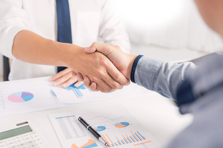 Business Meeting agreement Handshake concept, Hand holding after finishing up dealing project or bargain success at negotiation over office background.