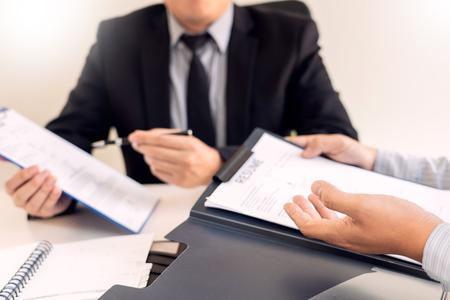 Entrevista de trabajo y concepto de contratación, candidato a nombramiento Hombre de negocios que explica su perfil y respuesta al gerente de recursos humanos sentado en una mesa frente a la oficina Foto de archivo