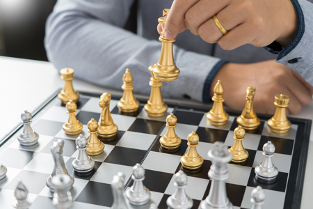 victory leader and success concept, business man playing take a checkmate figure another king with team on the chess board and thinking about strategy or management intelligence and education.