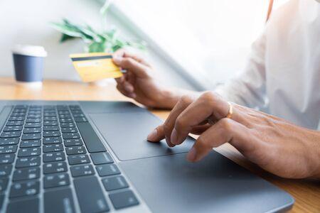 Mann, der mit Kreditkarte bezahlt und Sicherheitscode für Online-Shopping eingibt, eine Zahlung tätigt oder Waren im Internet mit Laptop-Computer kauft, Online-Shopping-Konzept.