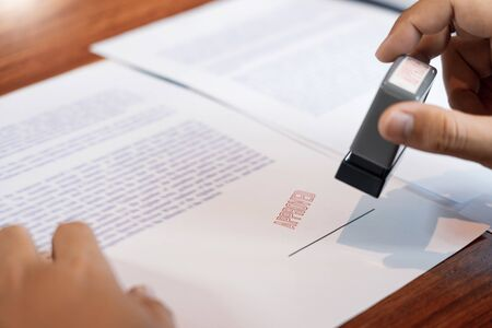 businessman Hand notary public hand ink appoval stamper Stamping seal On Approved Contract Form documents contract, loan money concept