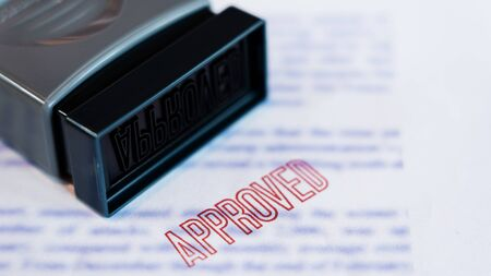 Document that has been stamped printed on Approved in large diagonal red text and rubber stamp, Business credit concept