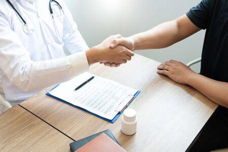Medicijngezondheidszorg en vertrouwensconcept, arts schudt handen met geduldige collega na het praten over medische onderzoeksresultaten