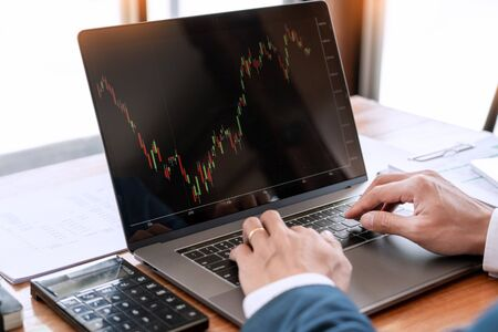 businessman or broker looking at computer laptop analysing about stock market invest trading stocks graph analysis candle line in office room. Reklamní fotografie