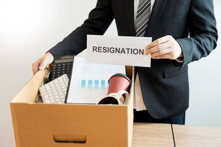Businessperson carrying packing personal company on brown cardboard Box and resignation letters for quit or change of job leaving the office, unemployment, resigned concept.