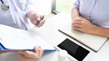 Doctor explaining and giving a consultation to a patient medical informations and diagnosis about the treatment for condition in hospital, medical ethics concept