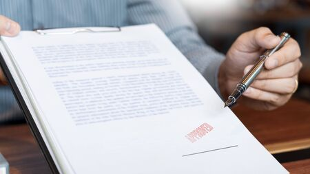 männlicher Punkt zur Unterzeichnung eines Geschäftsdokuments zum Aufbringen von Unterschrift, Füllfederhalter und genehmigtem Stempel auf einem Dokument, Zertifikatvertragsvereinbarung Anwaltshandkonzept Standard-Bild