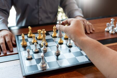 Business man take a king figure checkmate on the chess board game - strategy, management or leadership success concept Banco de Imagens