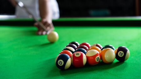 Man's hand and Cue arm playing snooker game or preparing aiming to shoot pool balls on a green billiard table