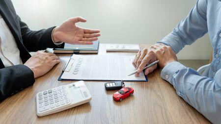 Agentenmakler, der ein Dokument mit einem Transportvertragsformular für den Kunden im Besitz des Kunden und den Verkäufer mit Autoschlüssel hält