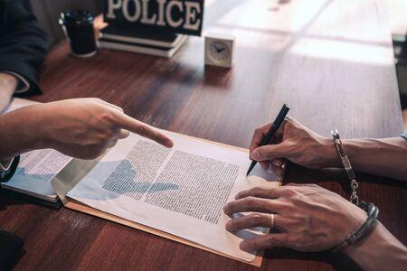 Polizist, der einen Verdächtigen oder einen kriminellen Mann mit Handschellen verhört, der bei der Untersuchung festgenommen wurde