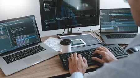 Programador que trabaja en la computadora en la oficina de TI escribiendo codificación de datos en el software y comprobando el código en la pantalla de la computadora