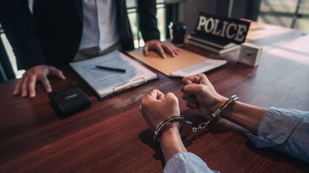 suspect with handcuffs being interviewed in interrogation room by Police officer, Criminal law concept Stock Photo