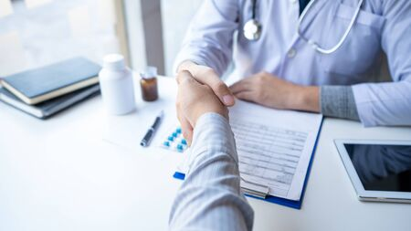 Medicine healthcare and trust concept, doctor shaking hands with patient colleague after talking about medical examination results Фото со стока