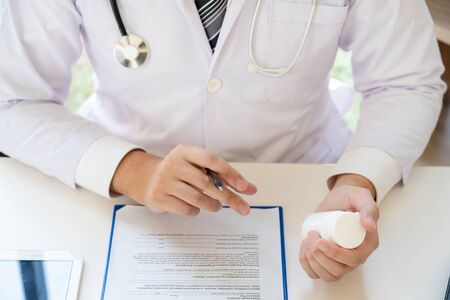 Doctor reading on a document report and writing on paperwork and searching treatment information at office, Medical healthcare concept