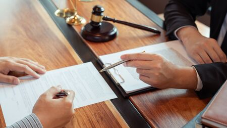 Lawyer working with client discussing contract papers with brass scale about legal legislation in courtroom, consulting to help their customer