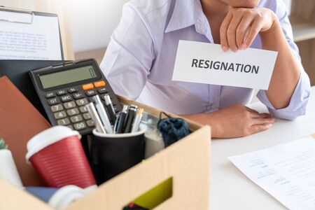Stress of business woman packing brown cardboard box her belonging after resign and signing cancellation contract letter, Change of job unemployment or resignation concept Фото со стока