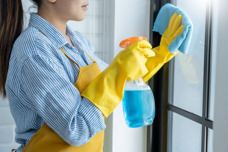 Young asian Woman in bright yellow gloves Washing or Cleaning Window the glass with blue rag wipe and detergent of her apartment from dust and stains