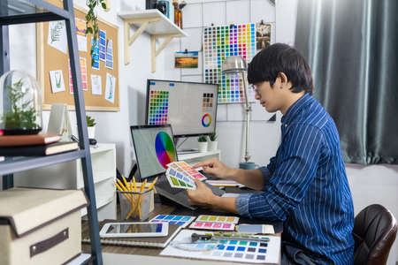 Asian men Architect or graphic designer designing a layout selection swatch samples for coloring screen graphics at work for renovation, Creative Occupation Design Studio concept