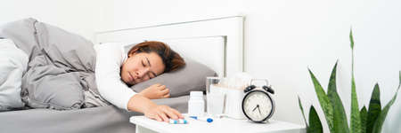 sick Asian woman lying in bed take medicines pills and glass of water from bedside table to relieve symptoms