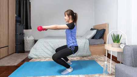 Attractive and healthy young Asian woman doing exercising at home during workout in comfy clothes on a mat in her bedroom, healthy lifestyle concept.