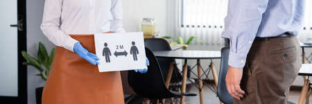 The waitress held a sign that explained the social distancing to customers for prevent the spread of pandemic Covid-19 or Coronavirus at restaurant, new normal concept. Stock fotó