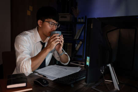 Attractive young asian businessman concentrated working until late overtime on publication at his desk in dark modern office at night, Overworking concept Standard-Bild
