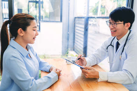 Charming Asian male doctor giving advice and medical informations and diagnosis to a female patient at consulting room in clinic Archivio Fotografico