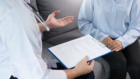 Asian female Patient listening intently to a male doctor explaining symptoms about health complaints in her home, health care concept.