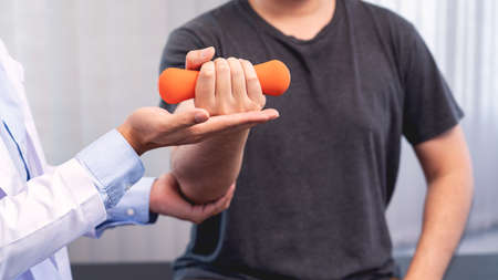 physiotherapist doctor rehabilitation consulting physiotherapy giving dumbbell exercising treatment with patient in physio clinic or hospital