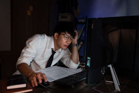 Feeling exhausted or Tired businessman working late on computer at office late in the evening night headache bad vision sight problem touching his forehead, stressful life and deadlines concept