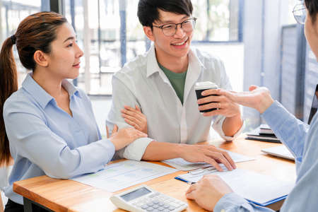 young Asian couple feeling happy and pleasant after received advice discussion about financial planning for investment at the meeting with financial advisor staff at home. Imagens