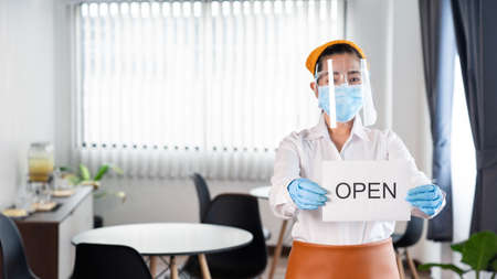Happy waitress with protective face mask holding open sign for the reopening at her restaurant after lockdown the quarantine coronavirus or covid-19 adapt to new normal