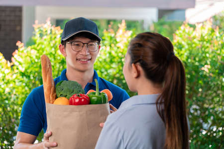 Asian deliver man in uniform handling bag of food vegetables and greens to customer at door home, food delivery concept