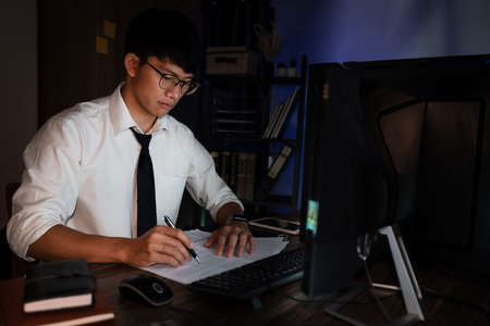 Young pensive asian man working late concentrated and serious in front of computer at night in dark office, Late night working or studying concept.