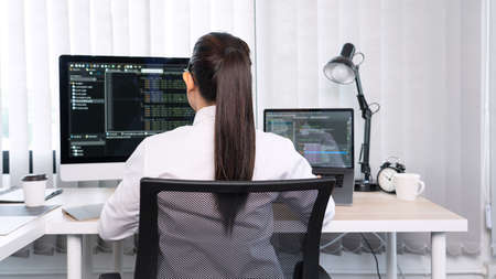 Asian Woman programmer typing source codes Programming On Computer in office, freelance web developer concept