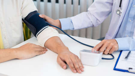 Medical concept a male doctor measuring blood pressure of patient by using sphygmomanometer before examination.