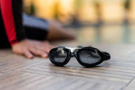 Sports and recreation concept black swimming goggles placed at a swimming pool with a boy wearing a swimming suit.