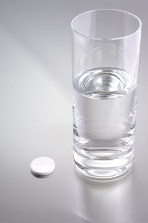 depressant: glass of water and aspirin on metallic background Stock Photo
